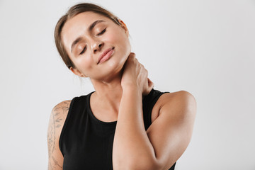 Image of brunette young woman touching her neck while doing workout