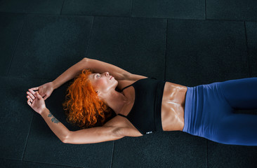 Lying down. Sporty redhead girl have fitness day in gym at daytime. Muscular body type