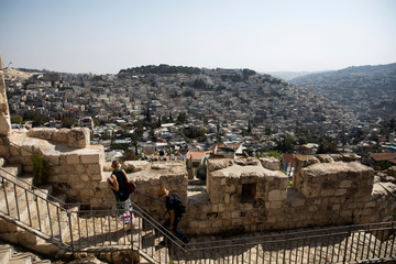 The Palestinian neighborhood of Silwan is seen in the background as people walk on a promenade on the surrounding walls of Jerusalem's Old City
