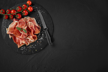 Sliced jamon, cherry tomatoes, herbs, spices and a knife on black stone slate board against a dark grey background. Close-up shot. Top view.