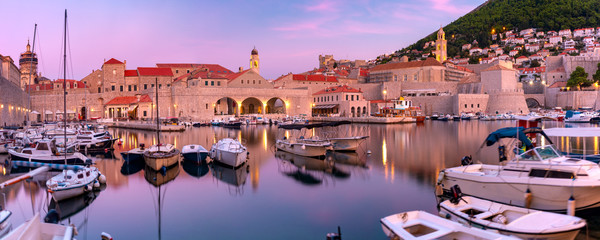 Poster Salmon Panoramic view of Old Harbour with boats and Old Town of Dubrovnik at sunset, Croatia