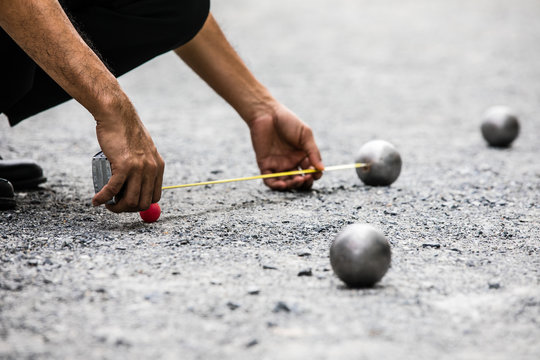 Man measuring the distance of petanque ball in petanque field