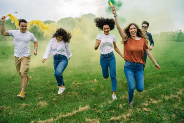 Group of five friends runs in a park with two smoke bombs at the park - Millennials have fun together in the summer at sunset Papier Peint