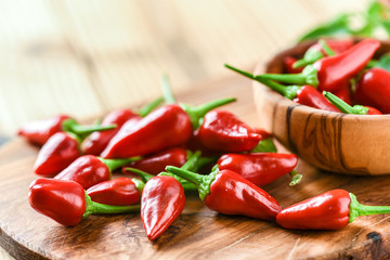 Papiers peints Hot chili Peppers Red hot peppers in old wooden bowl side view. Chili spicy pepper on table copy space.