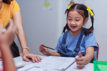 An Asian elementary school girls are studying mathematics in the classroom with an Asian female...