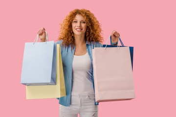 attractive girl holding shopping bags, Isolated On pink