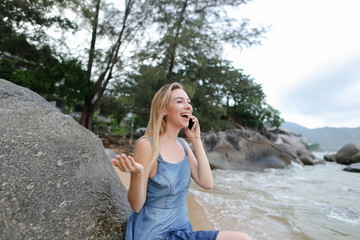 Fotobehang UFO Young blonde girl sitting on sand near sea and stones, talking by smartphone and showing thumbs up.