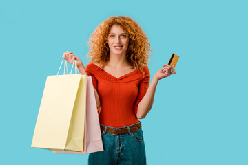 smiling woman holding shopping bags and credit card, Isolated On blue
