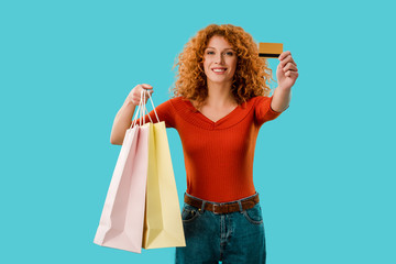 happy girl holding shopping bags and credit card, Isolated On blue