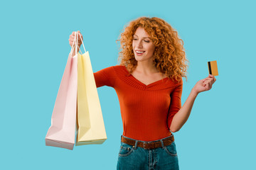 beautiful girl holding shopping bags and credit card, Isolated On blue
