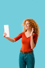 smiling woman waving and having video call on digital tablet isolated on blue