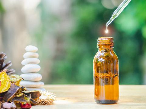 The essential oil falling from glass dropper into organic bio alternative medicine, brown bottle.