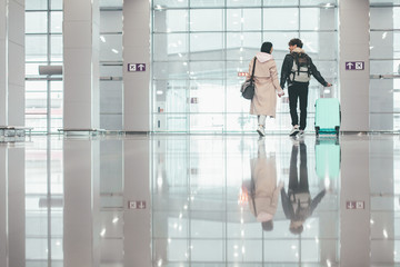White picture of man and woman walking in airport together and holding hands each other. Guy hold hand of suitcase. Daylight. Going to vacation or trip. Travelers.