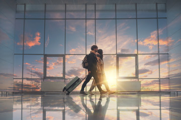 Picture of young couple walking in aurport close to window. Sunset outside. Going for a trip or vacation. Travel together. Take suitcase and backpacks.