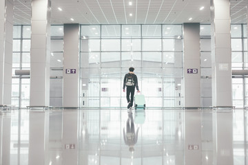 White picture of lonely single man walking inside airport hall. Waiting for flight. Business trip or vacation. Carrying backpack and suitcase. Young hipster in modern urban building.