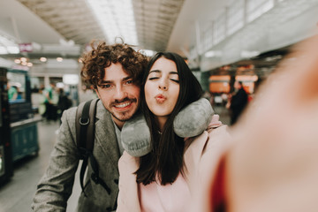 Selfie of young cheerful couple travel together. Waoman hold camera and send kisses. Positive attractive guy look straight and smile. She has travel pillow around neck. Inside airport.