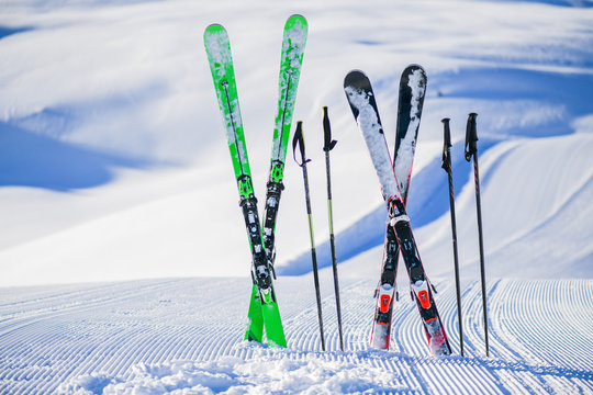 Skis in snow in winter season, mountains and ski items or equipments on the top in dolomites,