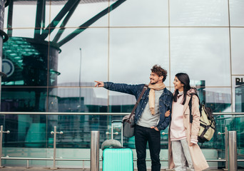 Picture of young man and woman stand outside or airport together and close to glass wall. Guy point. They look in one direction. Travel abroad. Vacation or honeymoon.