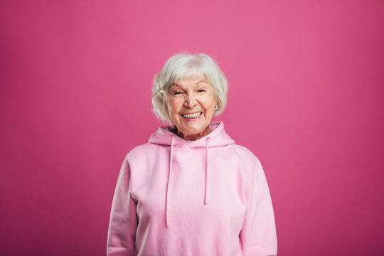 Happy cheerful positive old woman smiling wide and look straight on camera. Stand straight. Modern stylish senior model with grey hair. Isolated over pink background.