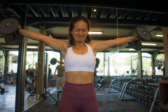 fitness lifestyle portrait of young attractive and athletic Asian Indonesian woman training hard working out at gym lifting weight dumbbells sweaty in sport bodybuilding concept