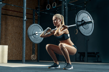Indoors shot of muscular young woman doing squats with barbell in a gym. Female bodybuilder doing workout Confident young blonde woman doing crossfit workout in gym Powerful attractive woman