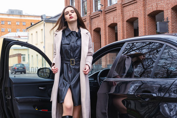 a young woman stands next to her car in the Parking lot. The girl is wearing a leather black dress and autumn coat. The concept of girls with the character and dangerous driving.