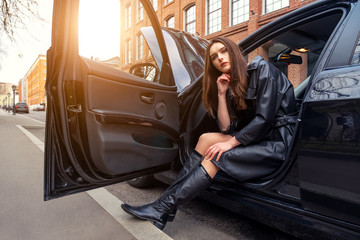 a young woman sits in her car in the Parking lot. young woman bored in her broken down car in the Parking. On young girl leather women black color of. Concept of girl with character and dangerous