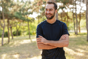 Sports man posing outdoors in nature green park. Papier Peint