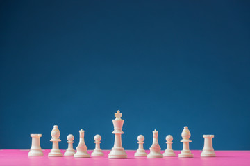 White chess figures positioned on pink board with king piece as the lead