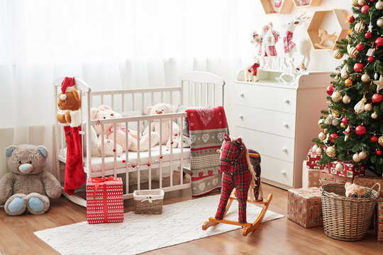 Christmas nursery, Christmas decor in children's bedroom, children's playroom decorated for new year, white children's bedroom, Christmas toys and gifts in children's bedroom, white bed with soft toys