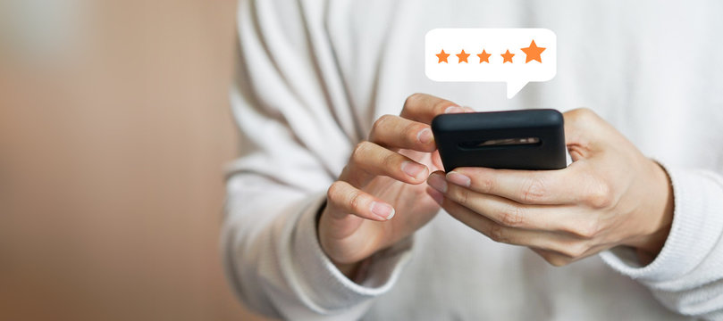 close up on customer man hand pressing on smartphone screen with gold five star rating feedback icon and press level three rank (good) for give score point to review the service business concept
