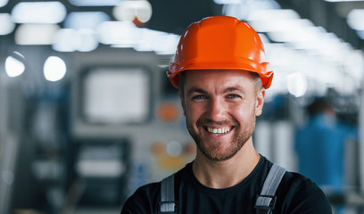 Smiling and happy employee. Portrait of industrial worker indoors in factory. Young technician with orange hard hat Fototapete