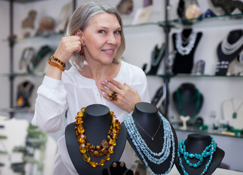 Adult woman chooses jewelry from turquoise and amber jewelery in the store