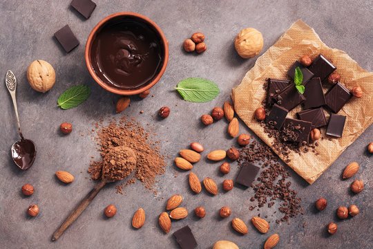 Chocolate, cocoa powder, a variety of nuts and mint leaves on a dark brown rustic background. View from above,flat lay.