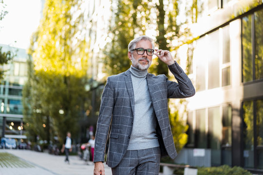 Fashionable mature, businessman on the go in the city