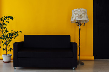black office sofa in the interior of the room with a yellow background
