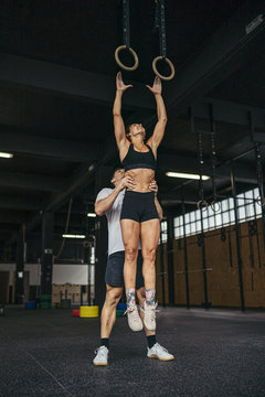 Young woman jumping to gymnastic rings, man helping her