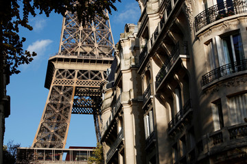 The Eiffel Tower stands near luxury Haussmannian buildings in the 7th arrondissement district of Paris