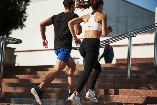 On the stairs. Man and woman have fitness day and running in the city at daytime