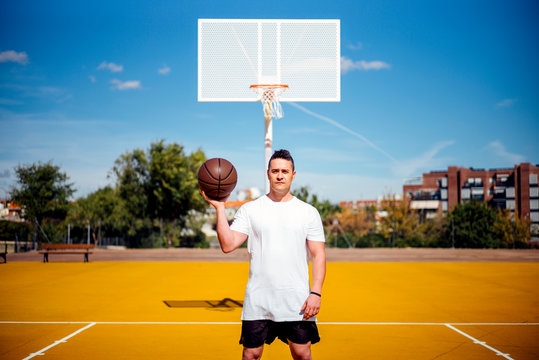 Basketball player posing at camera with the ball