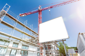 Blank white billboard in front of construction site with scaffolding and crane