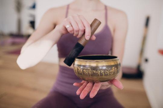 Young woman playing with tibetan bowl in yoga studio