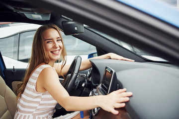 Leans on the steering wheel and smiling. Female driver inside of modern automobile. Testing brand new car