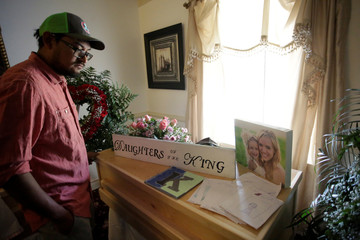 A man observes framed photographs of Rhonita Maria Miller and her four children during the funeral, members of the Mexican-American Mormon community killed by unknown assailants, in La Mora