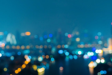Bokeh background of skyscraper buildings in downtown. Urban city with lights, Blurry photo at night time.  illuminated Cityscape Fototapete