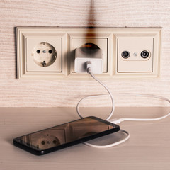 The charger of the mobile phone caught fire in the socket.
