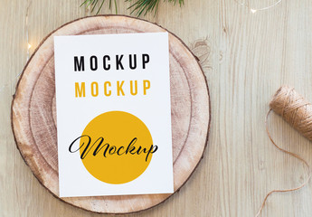 Vertical White Postcard on Wood Slice Top View Mockup