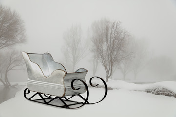 A silver sleigh on a snowy white background in the fog.  A extra large file size.