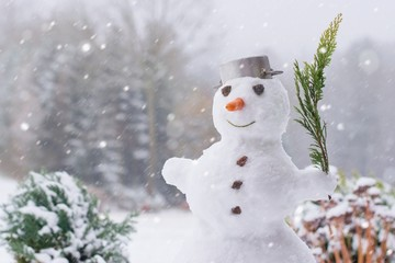 Lovely smiling snowman in the winter garden within a heavy snowfall