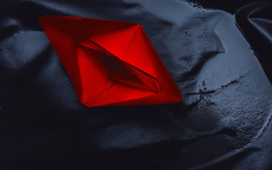 red paper boat on a black background